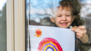 Little boy sticking a rainbow picture on a window