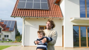Father and son outside their property with solar panels on the roof