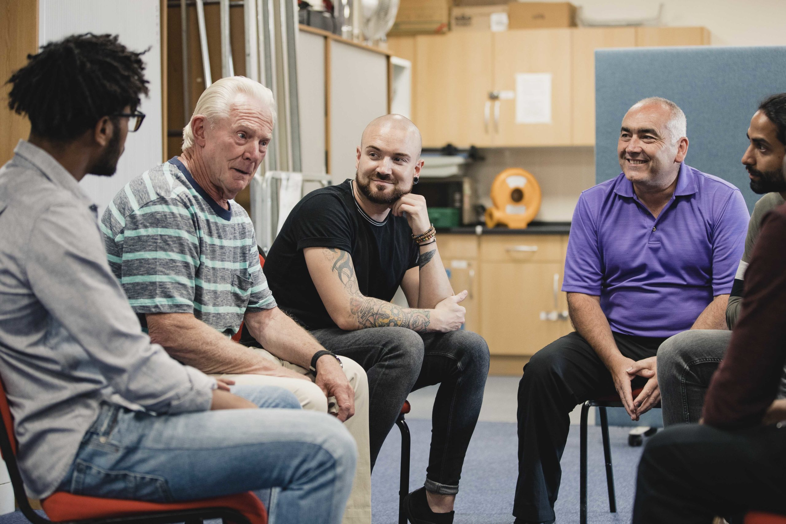 Diverse group of men are talking and laughing together in a mental health support group.