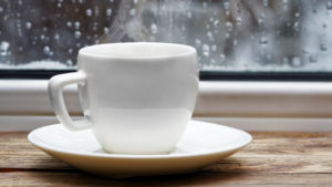 White cup of coffee on a window seal