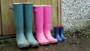 Three pairs of rubber (a.k.a wellington) boots arranged in size order in a garden setting. The boots are sized and styled for a male, female and child. The rubber boots are grubby and dirty, having been recently worn.