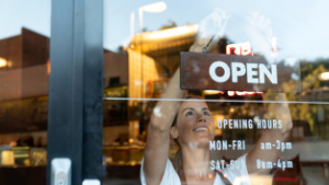Woman placing 'open' sign in cafe window
