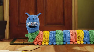 Knitted caterpillar draught excluder on hall floor