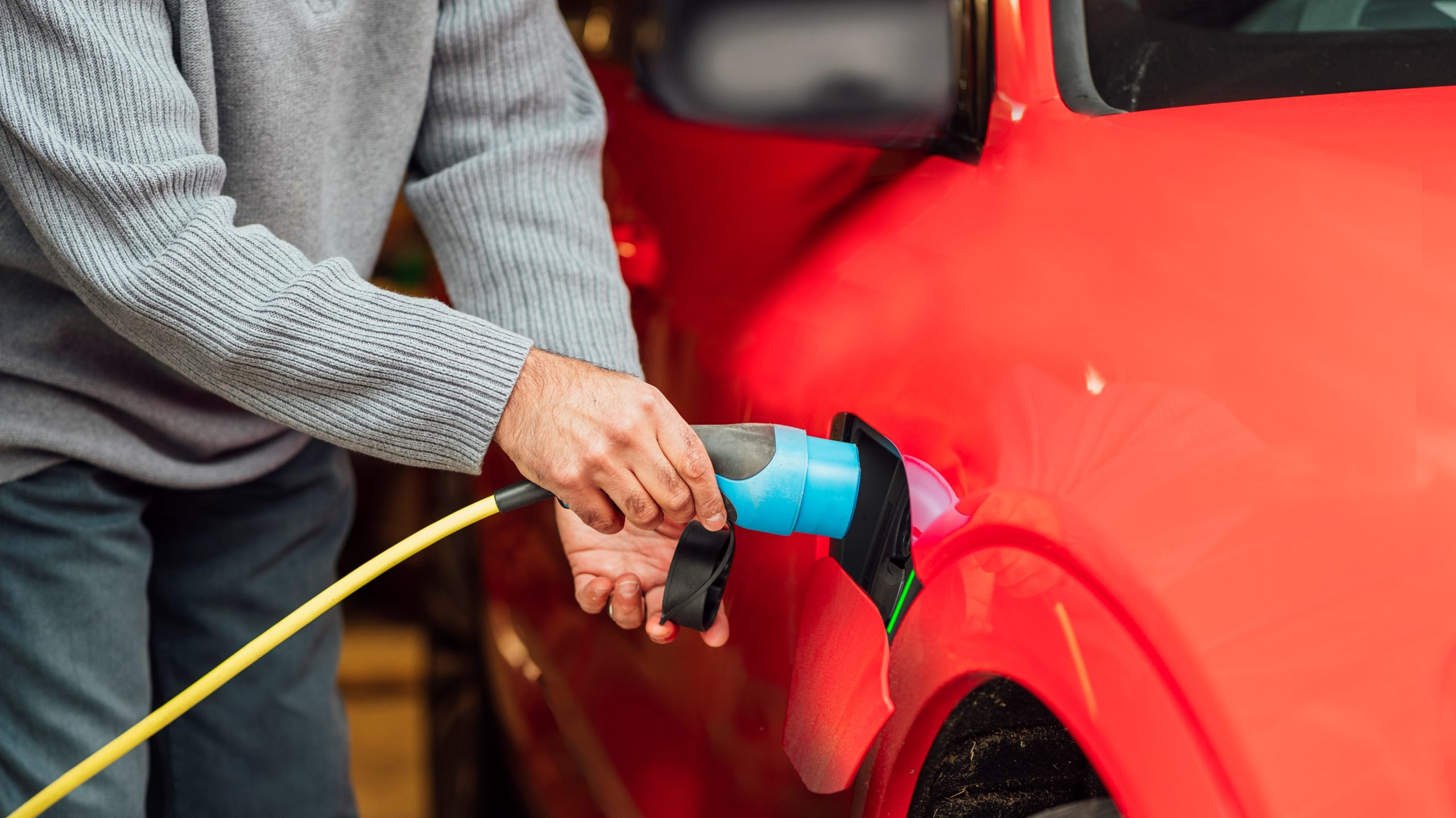 An unrecognizable person placing the charging port into the electric car they are an energy-conscious person using energy-efficient travel.