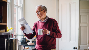 Man in kitchen looking at energy bill