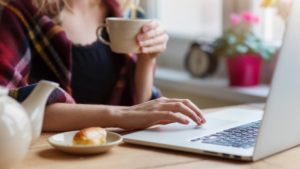Woman wrapped in blanket on laptop with hot drink