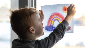 Young boy hanging rainbow drawing in window