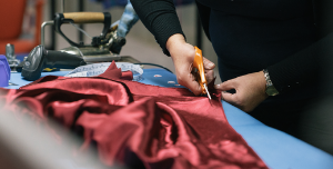 Person cutting fabric for clothing